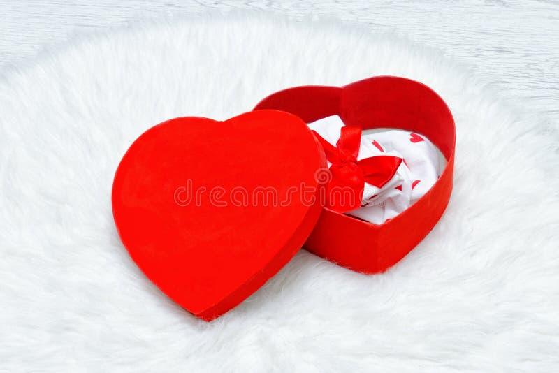 Rote Geschenkbox in Form des Herzens Unterwäsche und Kerzen stockfotografie