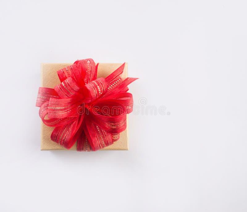 Rote Geschenkbox mit dem Goldbogen, lokalisiert lokalisiert auf weißem backgroun stockbild