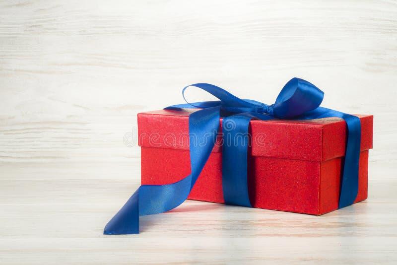 Rote Geschenkbox mit einem blauen Band auf einem Hintergrund von Weinlesebrettern lizenzfreie stockbilder