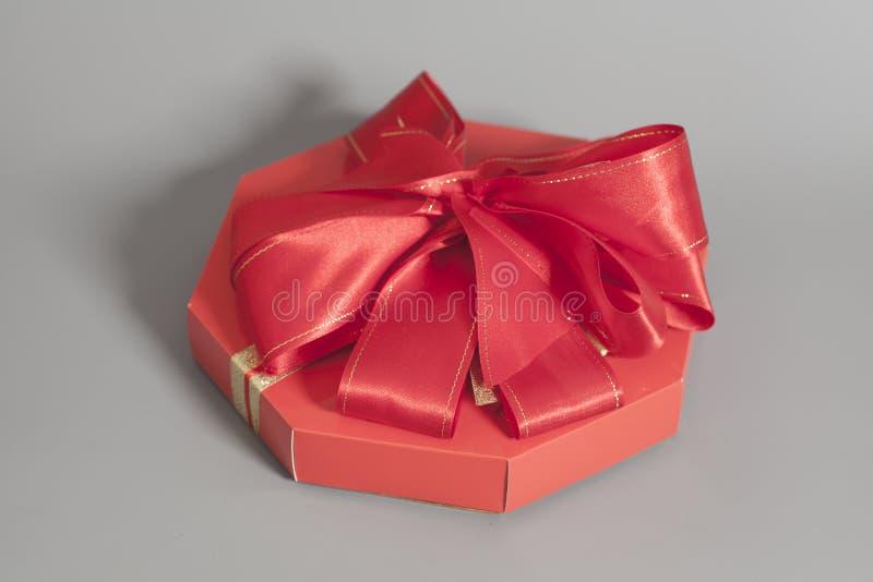 Rote Geschenkbox mit Süßigkeiten und Bandbogen stockfotografie
