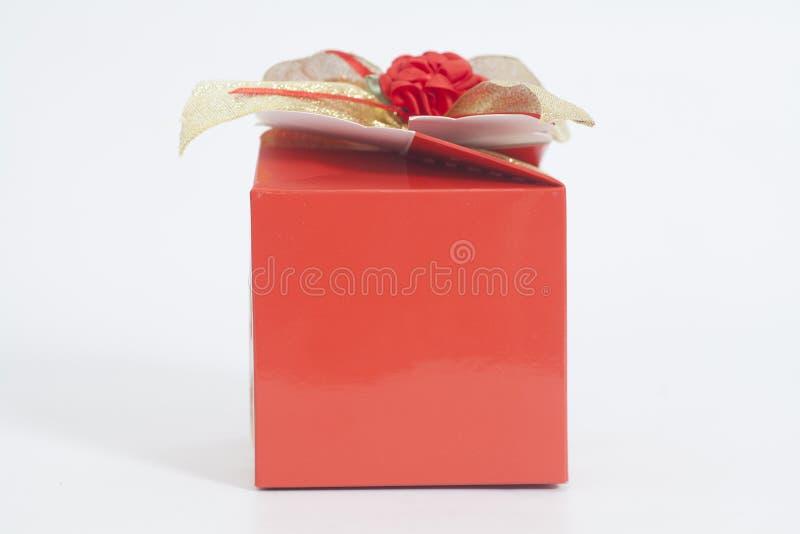 Rote Geschenkbox mit Süßigkeiten und Bandbogen stockbild