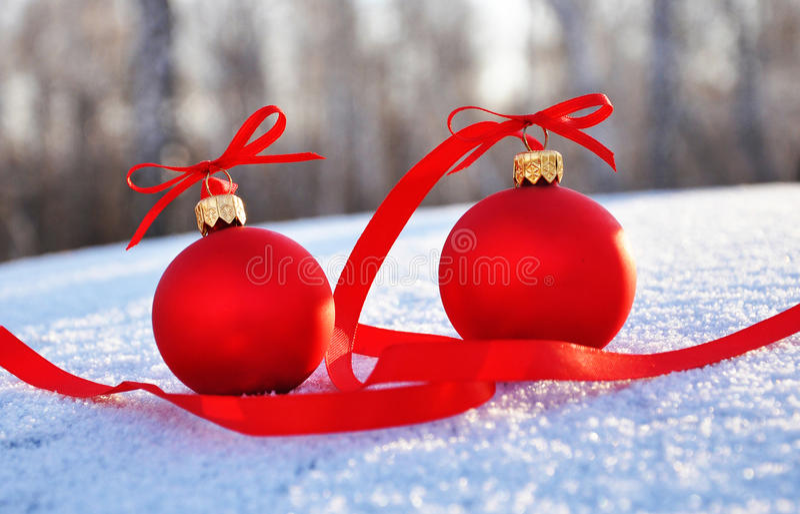 Rote Glasweihnachtskugeln auf Hintergrundschnee lizenzfreie stockfotos