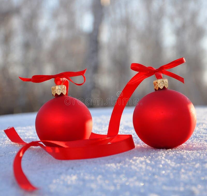 Rote Glasweihnachtskugeln auf Hintergrundschnee stockfotografie