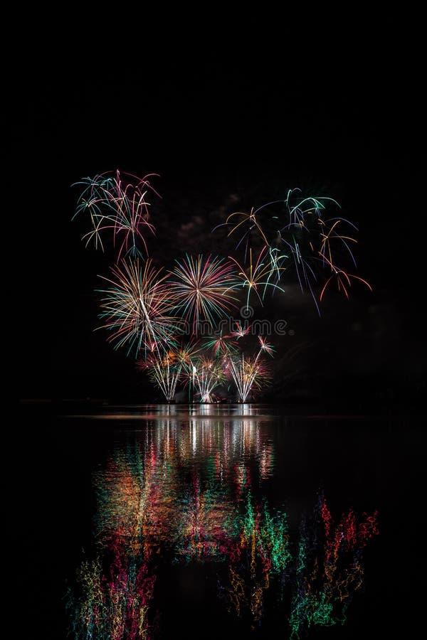 Rote, grüne und gelbe Sterne von den reichen Feuerwerken über Brnos Verdammung mit Seereflexion stockfotografie