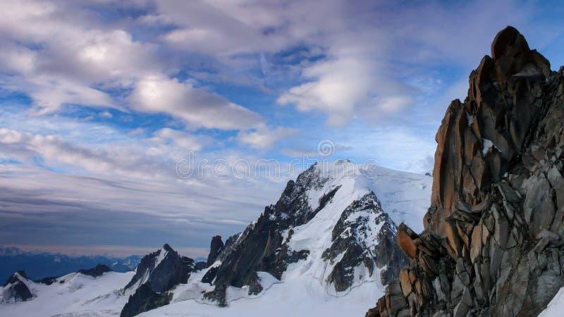 Rote Granitfelsennadeln mit einer großen Ansicht von Mont Blanc im Hintergrund in den französischen Alpen lizenzfreie stockfotografie