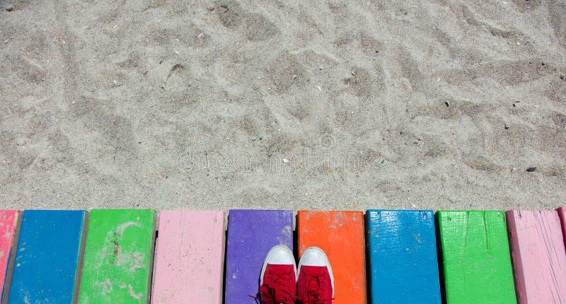 Rote Gummiüberschuhe auf Farbplanken auf einem Strand lizenzfreie stockbilder