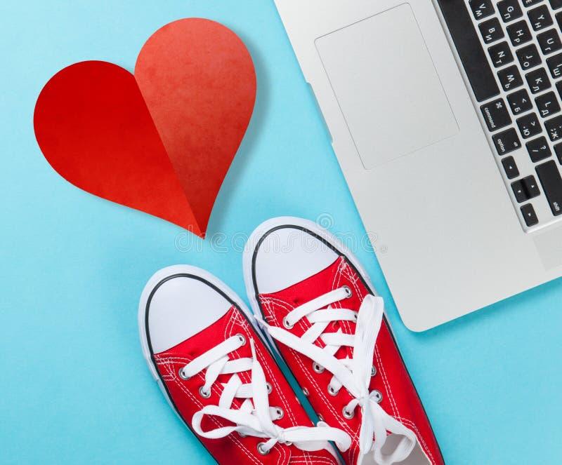 Rote Gummiüberschuhe und Laptop stockbild