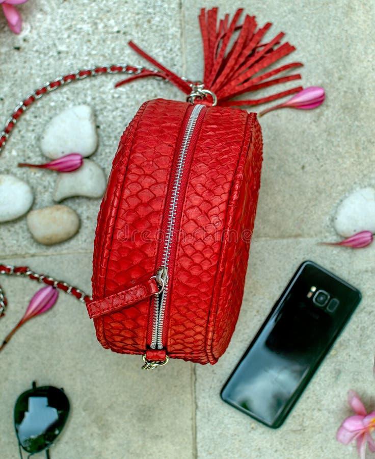 Rote handgemachte snakeskin Luxushandtasche, Blumen Frangipani, Sonnenbrille, Telefon Modefrauenzubehör Pythonschlangenschlange stockfoto