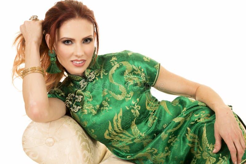Rote Hauptfrau im asiatischen Kleiderabschluß auf Sofa stockfotos