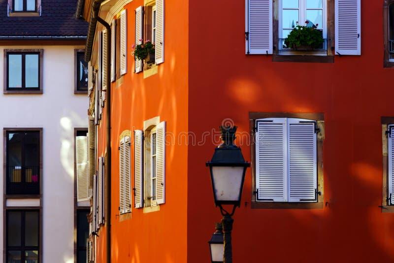 Rote Hausmauer mit schönen Fenstern und Fensterläden stockfotografie