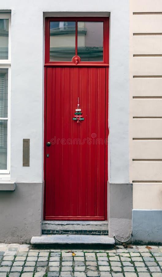 Rote Haustür der Weinlese verziert mit Weihnachtsbaumschmuck lizenzfreie stockfotografie