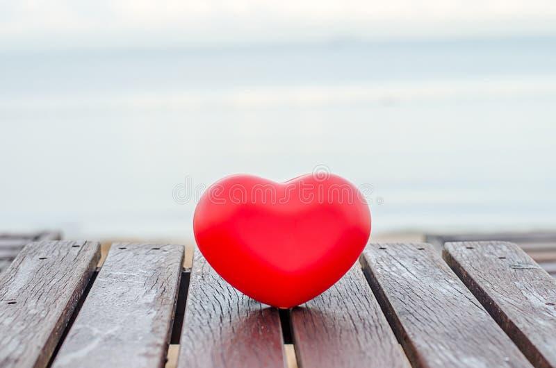 Rote Herzen auf der hölzernen Tabelle im Strand stockfotos