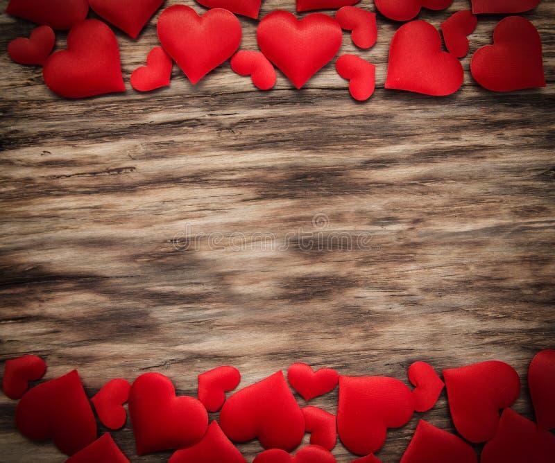 Rote Herzen auf einem hölzernen Hintergrund stockfotografie