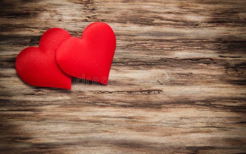 Rote Herzen auf einem hölzernen Hintergrund stockfotos