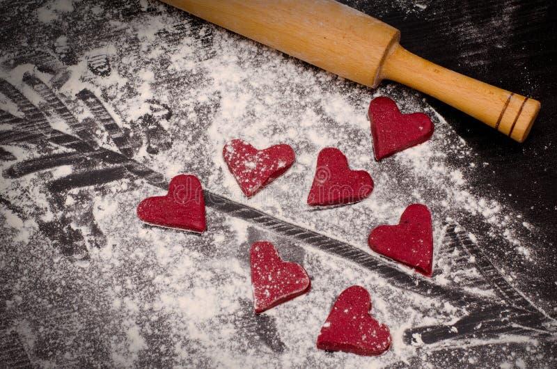 Rote Herzen gemacht vom Teig, vom hölzernen Nudelholz und von einem Pfeil gemalt auf Mehl lizenzfreies stockfoto