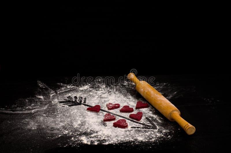 Rote Herzen gemacht vom Teig, vom hölzernen Nudelholz und von einem Pfeil gemalt auf Mehl Copyspace lizenzfreie stockbilder