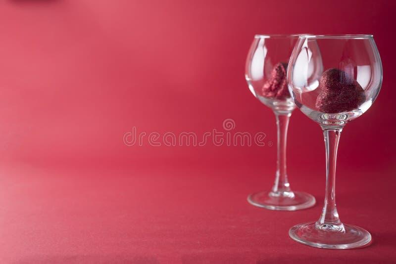 Rote Herzen in Gläsern auf rotem Hintergrund stockbilder