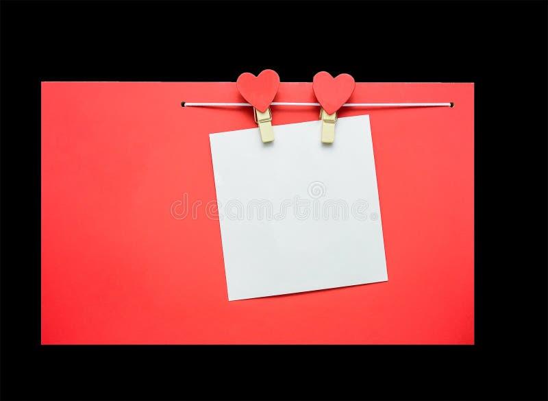 Rote Herzen mit den Wäscheklammern, die an der Wäscheleine lokalisiert auf schwarzem Hintergrund hängen lizenzfreies stockfoto