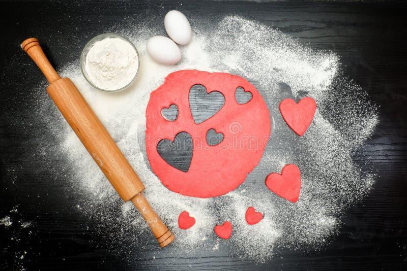 Rote Herzen schnitten Teig mit Nudelholz, Eiern und Mehl auf einem b heraus stockbilder