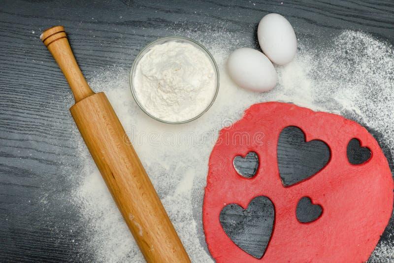 Rote Herzen schnitten Teig mit Nudelholz, Eiern und Mehl auf einem b heraus stockfotos
