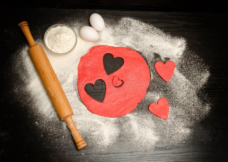 Rote Herzen schnitten Teig mit Nudelholz, Eiern und Mehl auf einer schwarzen Tabelle heraus Ansicht von oben Raum für Text lizenzfreie stockfotografie
