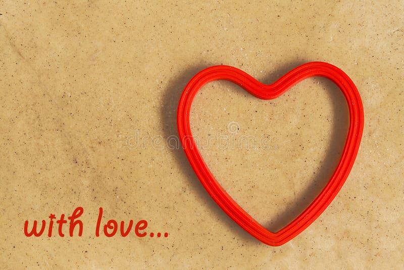 rote Herzform auf einem Hintergrund des Teigs mit Aufschrift lizenzfreie stockbilder