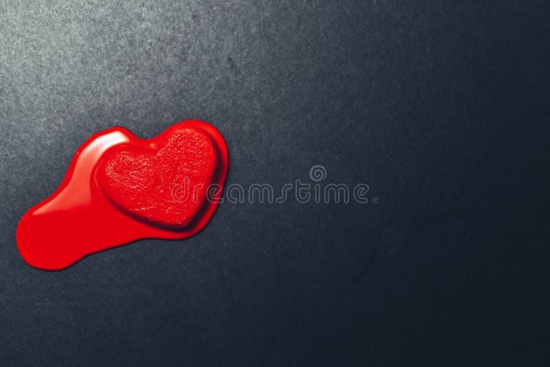 Rote Herzform-Eiscreme, die auf dunklem oder schwarzem strukturiertem Papierhintergrund schmilzt lizenzfreie stockfotografie