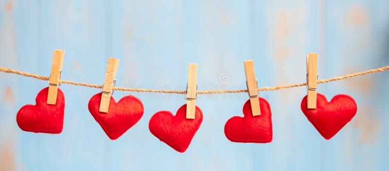 Rote Herzformdekoration, die an der Linie mit Kopienraum für Text auf blauem hölzernem Hintergrund hängt Liebe, Hochzeit, romanti stockfotos