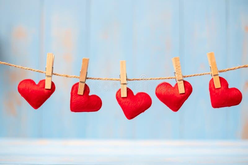 Rote Herzformdekoration, die an der Linie mit Kopienraum für Text auf blauem hölzernem Hintergrund hängt Liebe, Hochzeit, romanti lizenzfreies stockbild