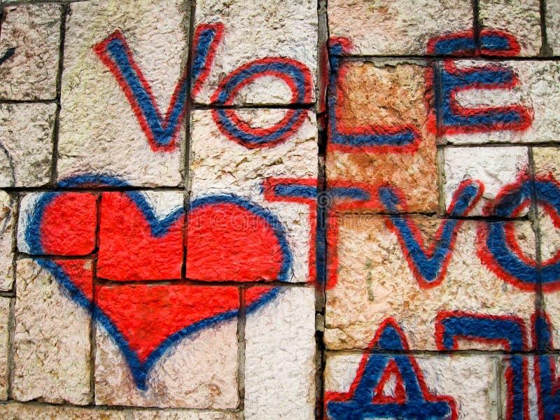 Rote Herzgraffiti auf Backsteinmauer stockbild