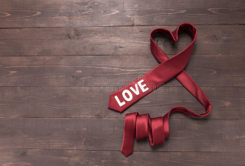 Rote Herzkrawatte ist auf hölzernem Hintergrund stockfotografie