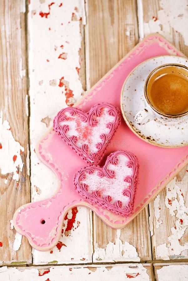Rote Herzplätzchen und Espresso Kaffeetasse auf altem Holztisch lizenzfreies stockbild