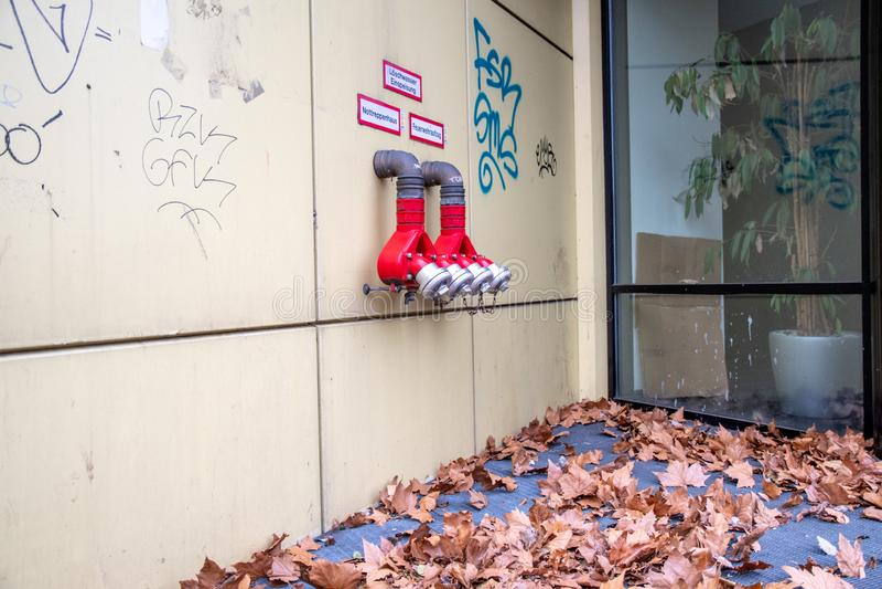 Rote Hydranten auf schmutziger Wand mit Ahornblättern auf dem Boden nahe Glasfensterwand in Berlin Germany stockbild