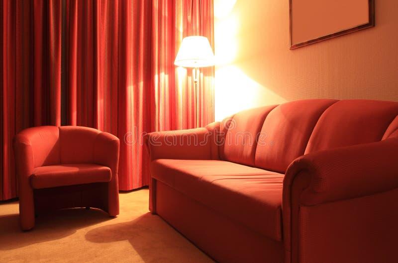 Rote Innencouch des Hotels, Lehnsessel, Fußbodenlampe stockfoto