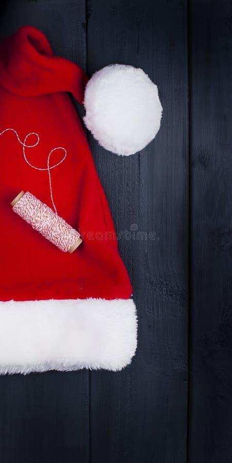 Rote Kappe mit Quast Santa Claus Auf einem schwarzen hölzernen Hintergrund, Geschenken und Weihnachtsdekor Freier Platz für Text  stockfoto