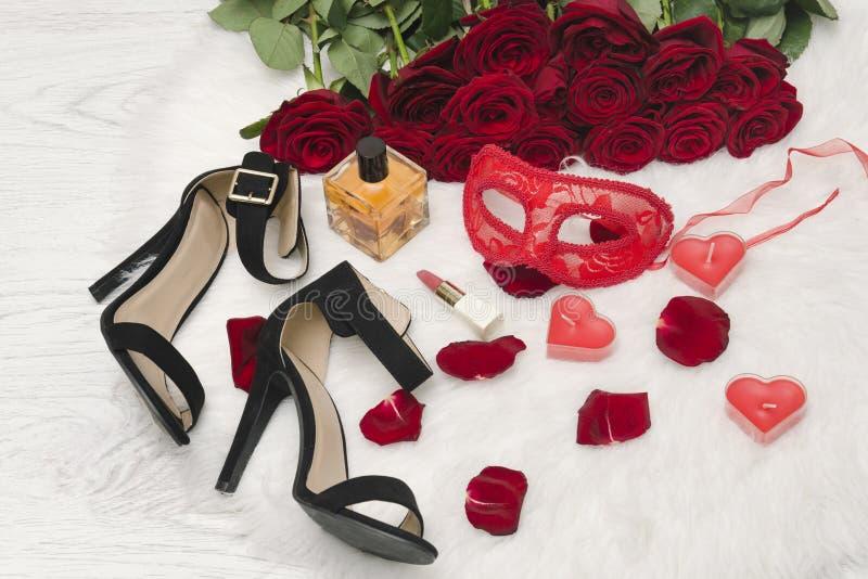 Rote Karnevalsmaske, ein Blumenstrauß von roten Rosen, schwarze Schuhe mit Fersen, Kerzen in Form eines Herzens, Lippenstift, Par lizenzfreies stockbild