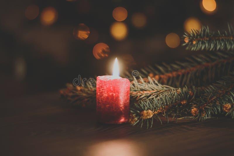 Rote Kerze auf Weihnachtsbaumhintergrund lizenzfreie stockfotografie