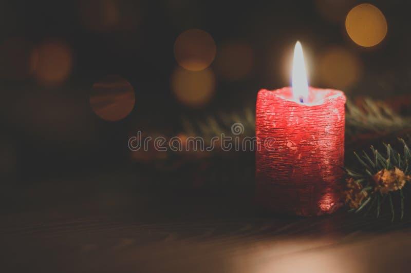 Rote Kerze auf Weihnachtsbaumhintergrund stockbild