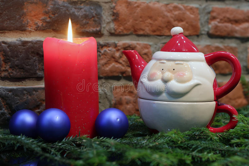 Rote Kerze, blaue Weihnachtsbälle und Santa Claus-Teekanne stockfoto