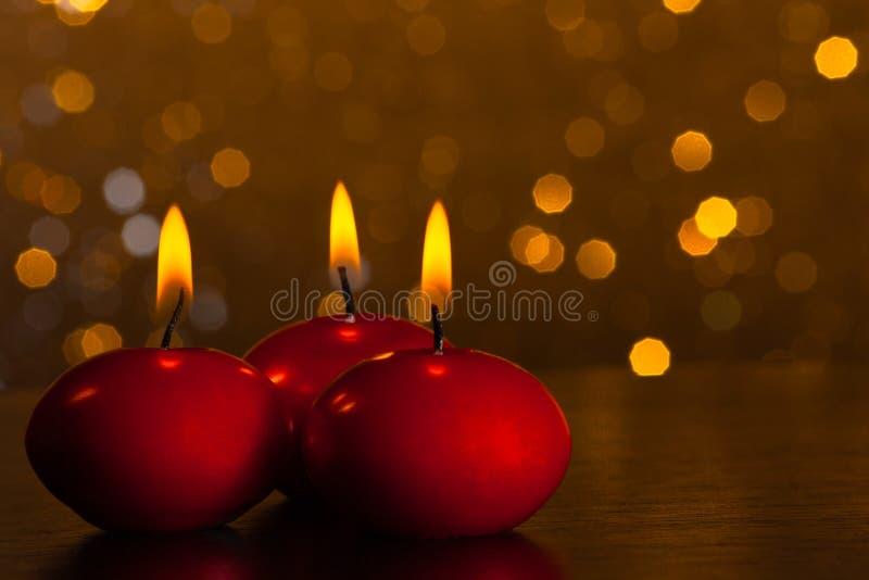 Rote Kerzen auf goldenem bokeh Hintergrund stockfotografie