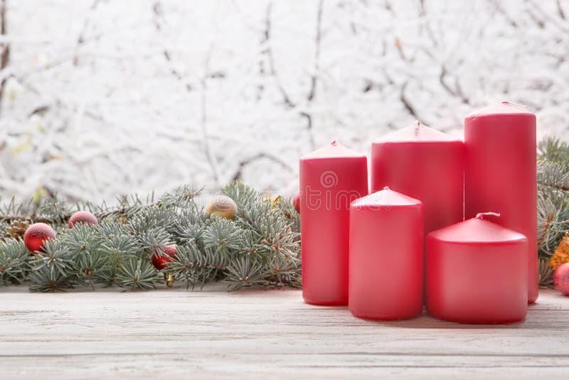 Rote Kerzen der Weinleselaterne mit Weihnachtstannenbaumgirlande auf hölzernem Brett auf Fensterbrett über schneiendem Baum der N stockfotos