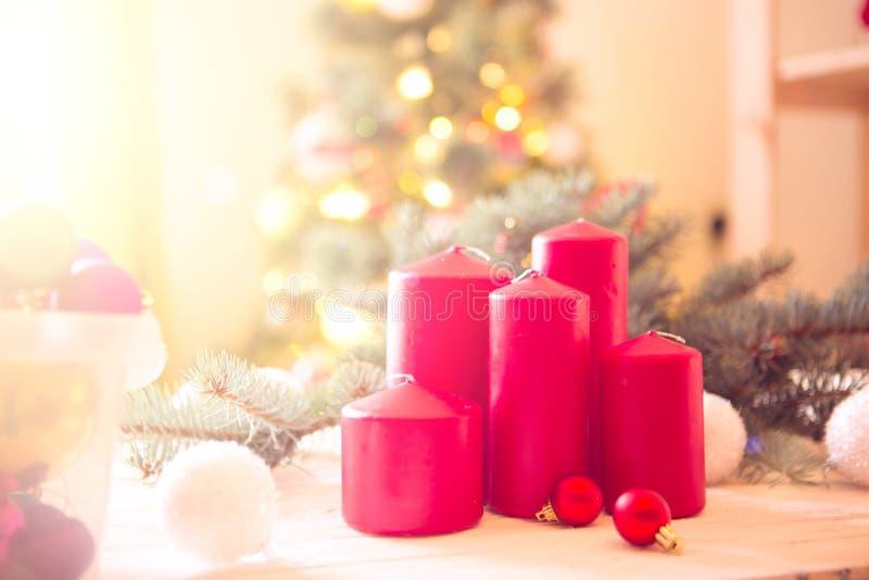 Rote Kerzen gegen Weihnachtsbaumhintergrund im Innenraum stockfotos