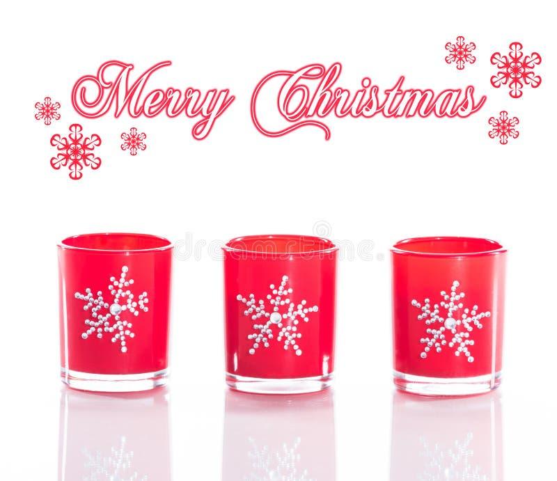 3 rote Kerzen, Kerzenhalter mit den Kristallschneeflocken lokalisiert auf reflektierendem weißem Plexiglashintergrund lizenzfreie stockfotografie