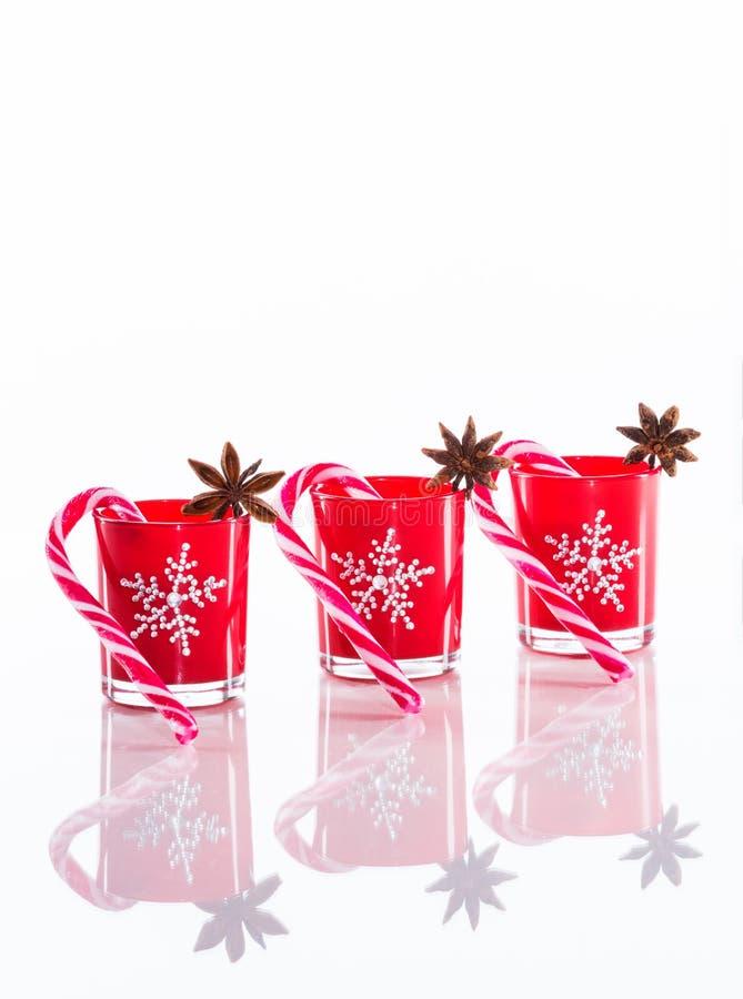 Rote Kerzen, Kerzenhalter mit Kristallschneeflocken und Zuckerrohre auf reflektierendem weißem Plexiglashintergrund mit Kopie spa lizenzfreie stockfotografie