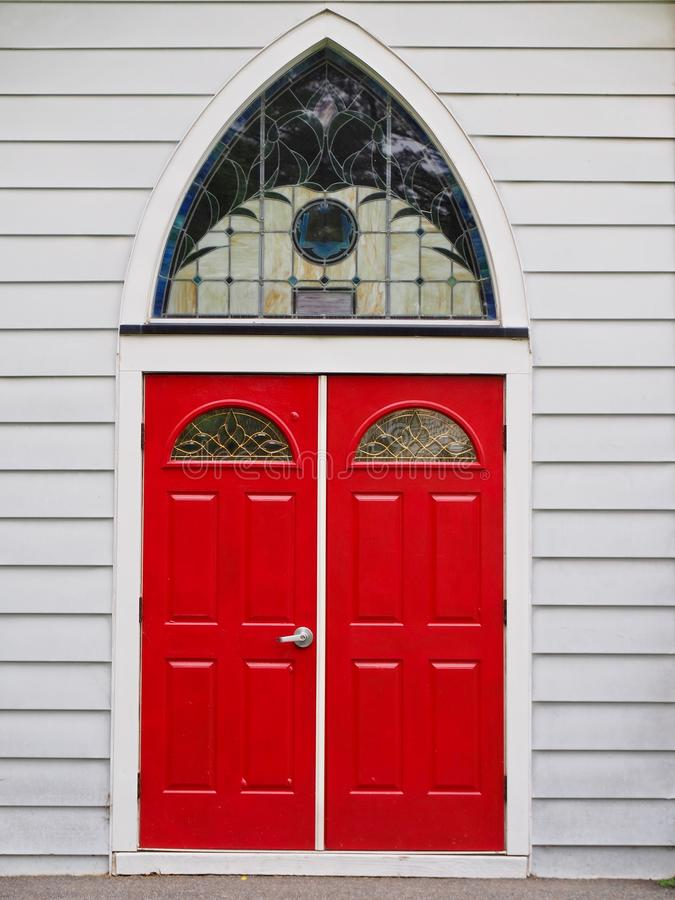 Rote Kirchen-Türen mit Reuleaux wölbten Fenster lizenzfreie stockfotografie