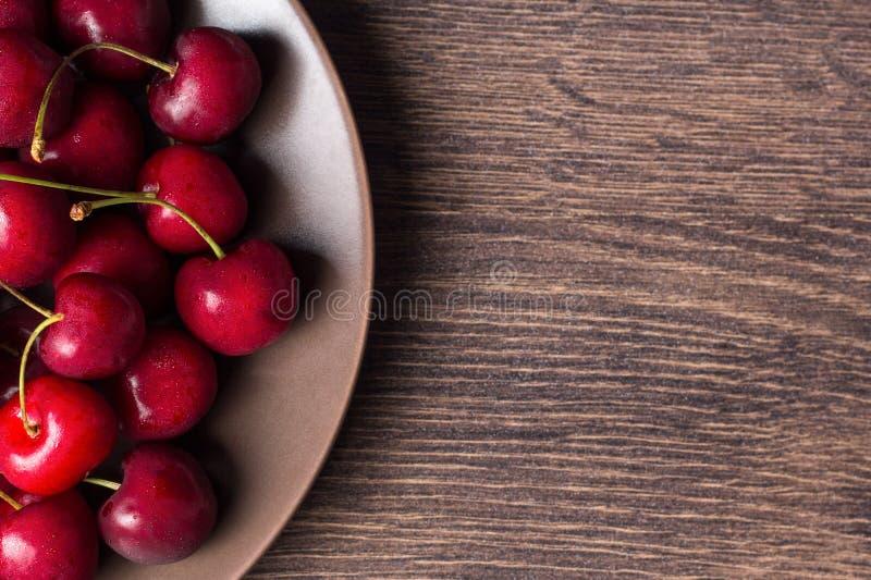 Rote Kirschen auf einer braunen Platte auf einem Holztisch Sommernahrung, gesunde Ernährung Organisch, vegetarisch, strenger Vege lizenzfreies stockfoto