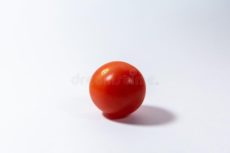 Rote Kirschtomate liegt auf einem weißen Hintergrund stockfoto