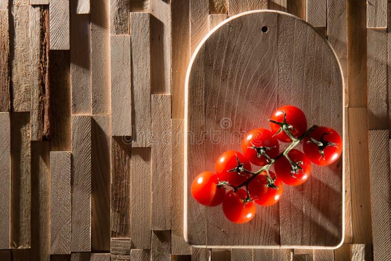 Rote Kirschtomaten auf hölzerner Platte stockfotos