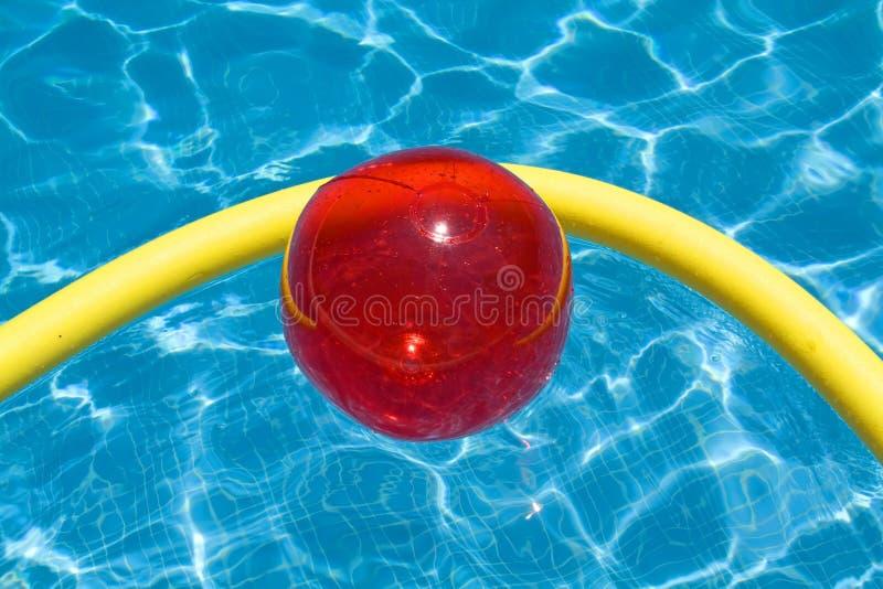 Rote Kugel im Pool lizenzfreie stockbilder