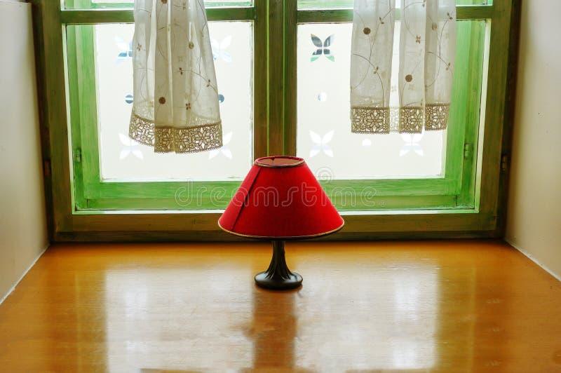 Rote Lampe der Weinlese mit Schatten auf Fenster lizenzfreie stockfotos
